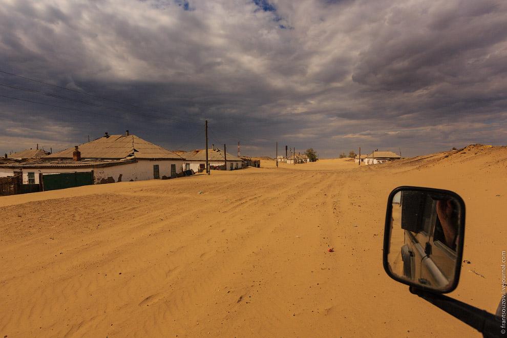 6. Песок засыпает заборы, его уровень доходит до окон — кажется, что здания словно погружаются