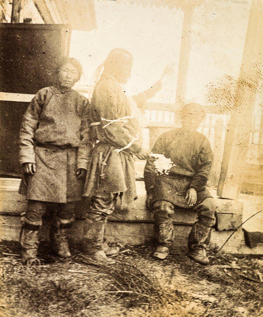 Трое мужчин нивхов, один из них шаман. Шаман проводит ритуал
