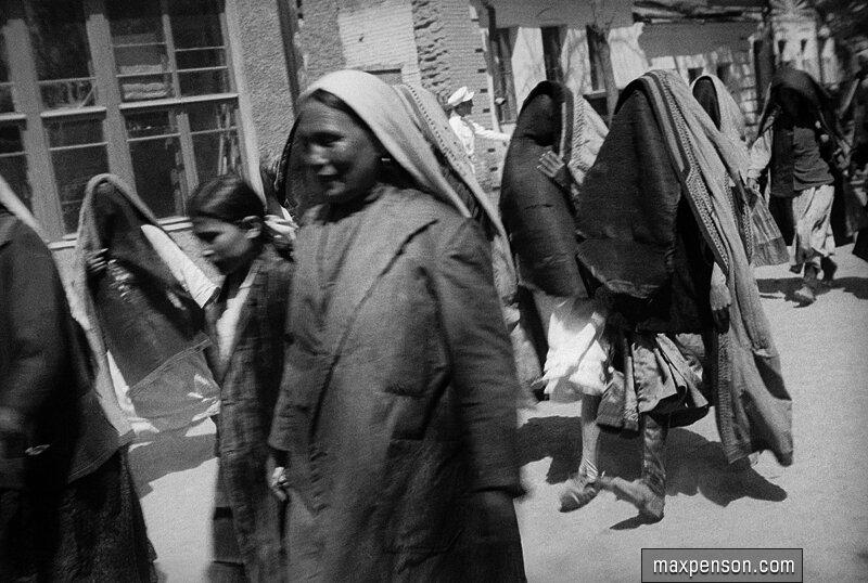 Группа женщин в паранджах на улице - двое с открытым лицом. Старый Ташкент