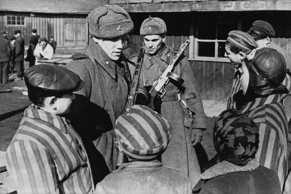Советские солдаты общаются с детьми, освобожденными из Освенцима. Польша. Январь 1945 г.