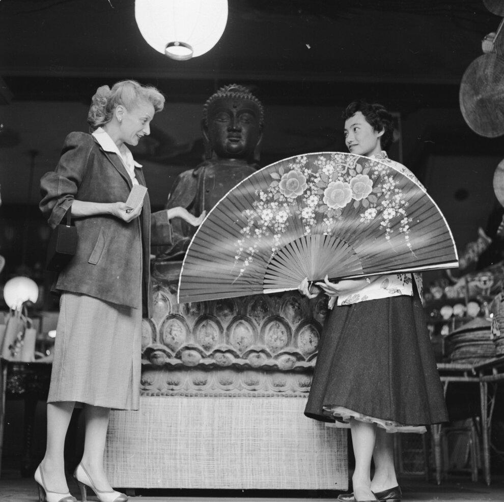 Продавщица в бутике компании Tai Ping на авеню Грант демонстрирует гигантский китайский веер для заинтересованных клиентов