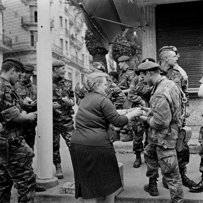 Une passante ravitaille les parachutistes de la 10e Division parachutiste (DP)