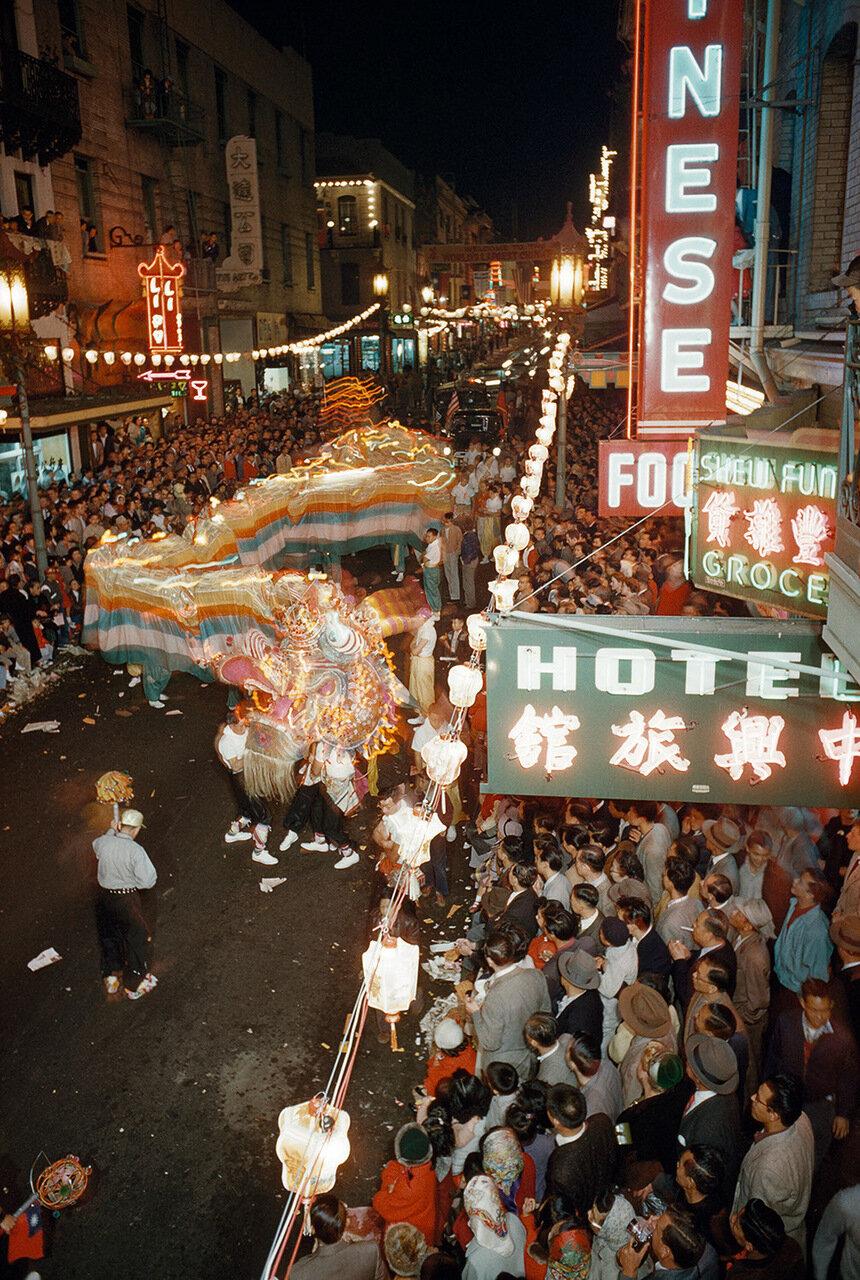Толпы собрались посмотреть 100 футового дракона на параде, проходящем по улице.