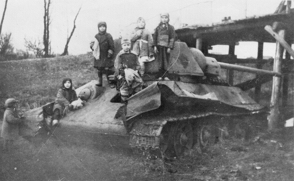 Дети на брошенном у моста советском танке Т-34-76. Фото не ранее осени 1942 года, так как танк оснащен башней-
