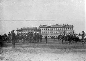 Батарея артиллерийской бригады проходит церемониальным маршем мимо императора Николая II и его свиты во время майского парада на Марсовом поле.