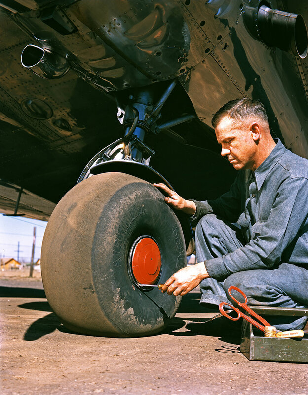 An aviation mechanic removing the hubcap from the wheel of a Lockheed Model 12A Electra Junior, belonging to Byrd-Frost Incorporated, at Dallas Love Field Airport in Dallas, Texas. March 1940