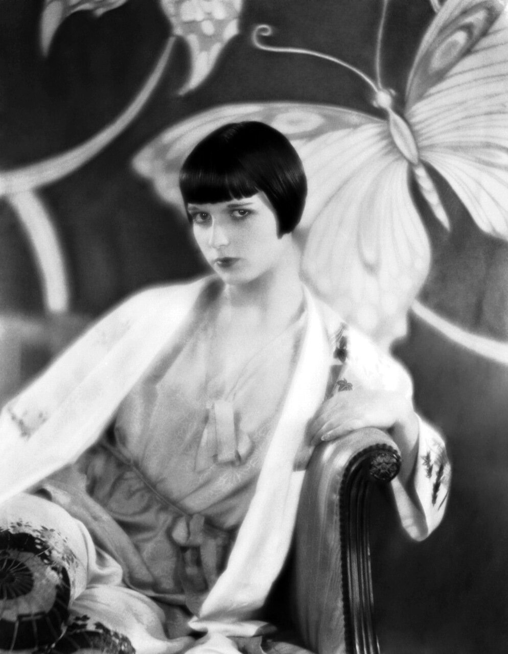 circa 1926: American actress Louise Brooks (1906 - 1985) sitting on an armchair in front of a screen decorated with butterflies. (Photo by Eugene Robert Richee)