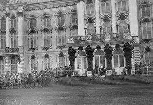 Император Николай II (справа), императрица Александра Федоровна и шеф полка великая княгиня Мария Павловна у подъезда Екатерининского дворца во время церемониального марша на параде полка.