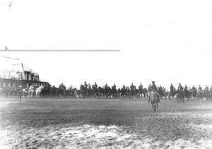 Высший офицерский состав принимает парад юнкеров-артиллеристов на военном поле.