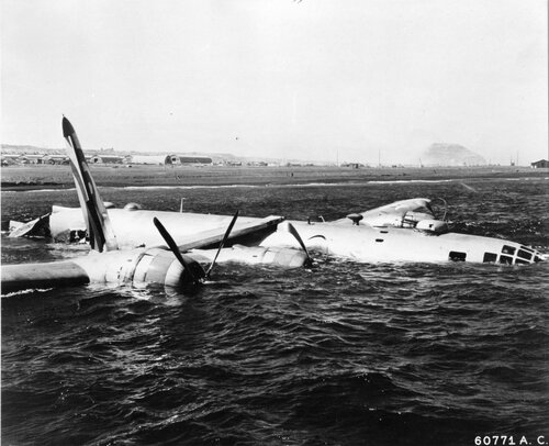 """This 6th Bomb Group B-29 """"Superfortress"""" found Iwo Jima fog-closed.  The plane was forced to ditch off the shore; but the crew swam to safety.  Bonin Islands."""