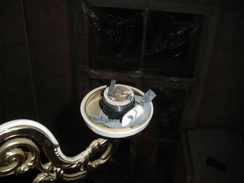 Фото 5. Осколки U-образной трубки «энергосберегающей» лампы на контактной части патрона и на основании плафона. Видна пружинная шайба, препятствующая ослаблению крепления плафона.
