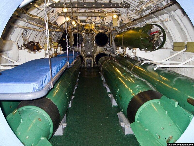 Подводная лодка С-189. Первый отсек - носовой, торпедный, жилой. Слева разложены койки экипажа. В походе они были с обоих бортов и в три яруса. Справа торпеды - внизу боевые, а сверху - маленькая торпеда-имитатор. После выстрела она шумела как подлодка и должна была отвлекать противолодочные корабли противника от настоящей подлодки.