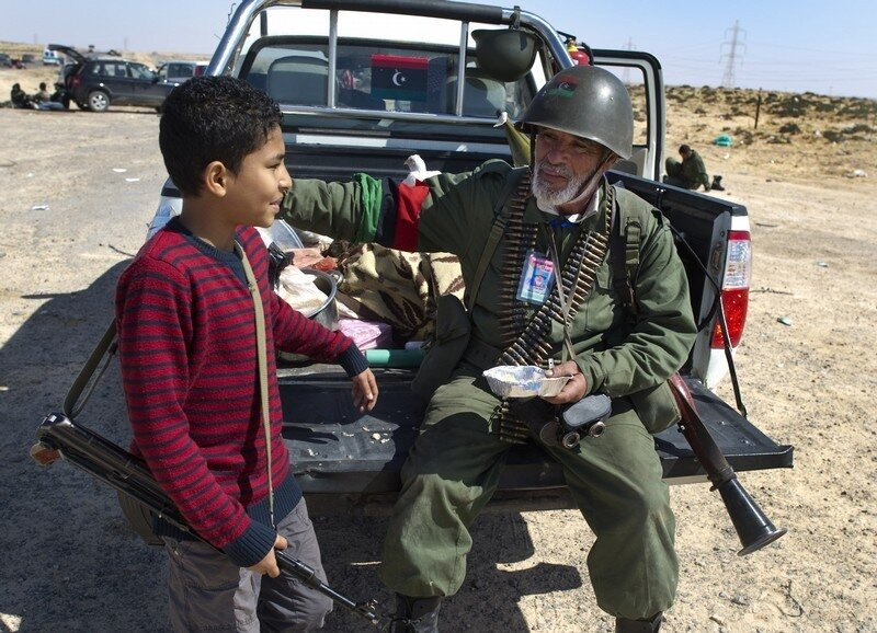 A Libyan rebel shares his lunch near Bre