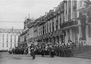 Император Николай II с группой командиров лейб-гвардии стрелковой бригады у подъезда Екатерининского дворца наблюдает за прохождением войск во время парада.