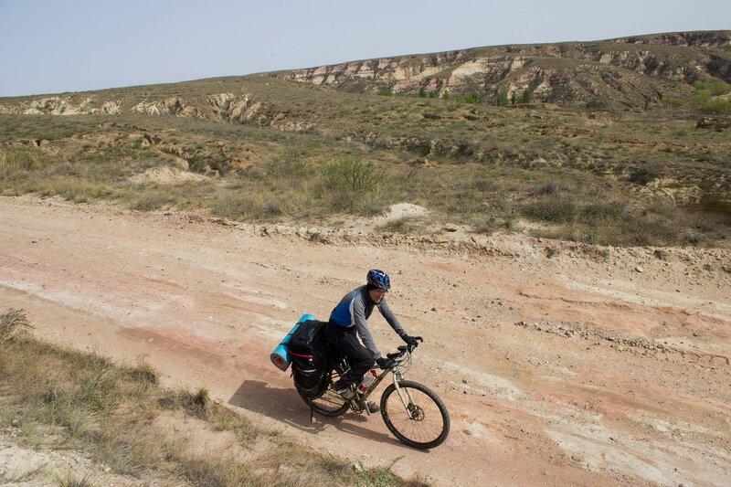 велосипедист едет по плато Ордос, Внутренняя Монголия, Китай