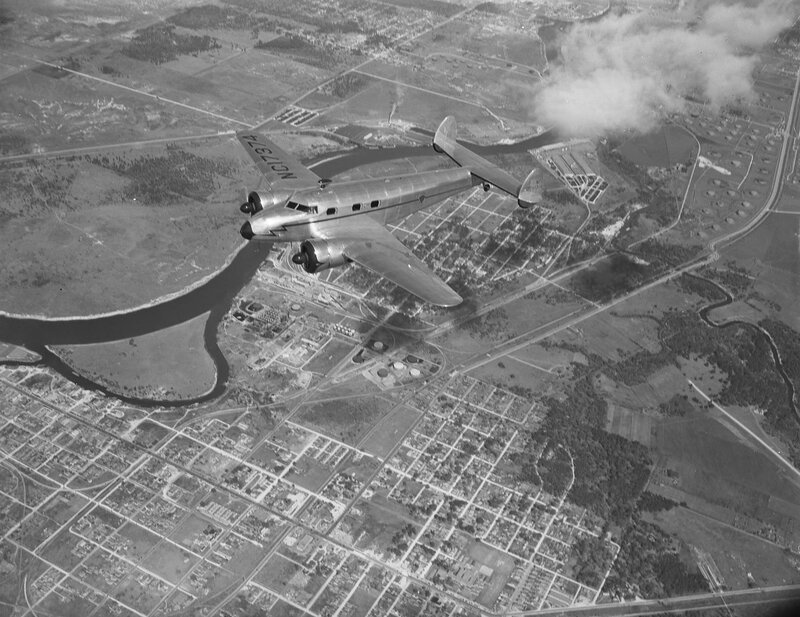 A Lockheed Model 12A Electra Junior, belonging to the Superior Oil Company, in flight over Houston, Texas. March 1940