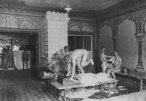Банщики моют посетителей в мыльне.