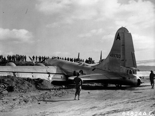 """Crowd gathers on embankment to look at 19th Bomb Group Boeing B-29 """"Superfortress"""", which crash landed on Iwo Jima, Bonin Islands; two engines were knocked out during raid over Osaka, Japan, 10 March 1945."""