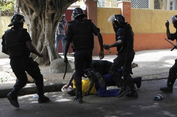 Riot police attack a demonstrator during a demonstration in Senegal's capital Dakar