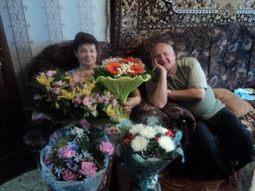 Именинница с цветами и мужем