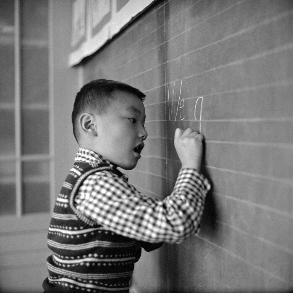 Маленький мальчик в школе Стоктон практикуется писать на доске.