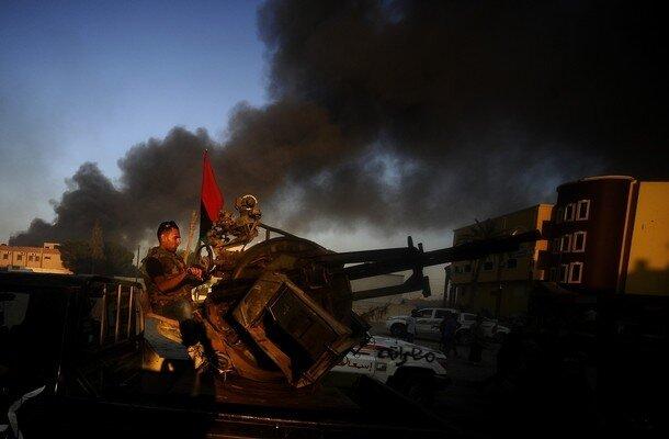 Rebel fighters maneuver their gun during
