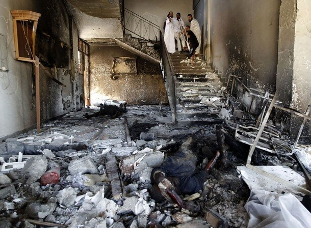 Rebels carry a man accused of being a mercenary fighting for Muammar Gaddafi, inside a fire station in Tripoli