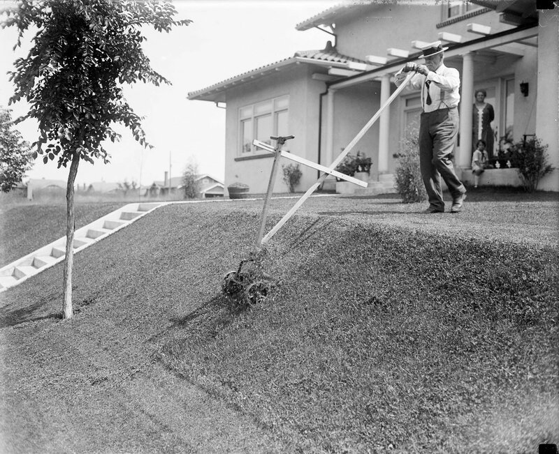 Harry F. Rhoads uses a lawn mower modified with an extended handle to mow a sloped lawn in Denver, Colorado, between 1920 and 1930