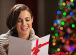 Smiling young woman reading christmas postcard in front of christmas lights