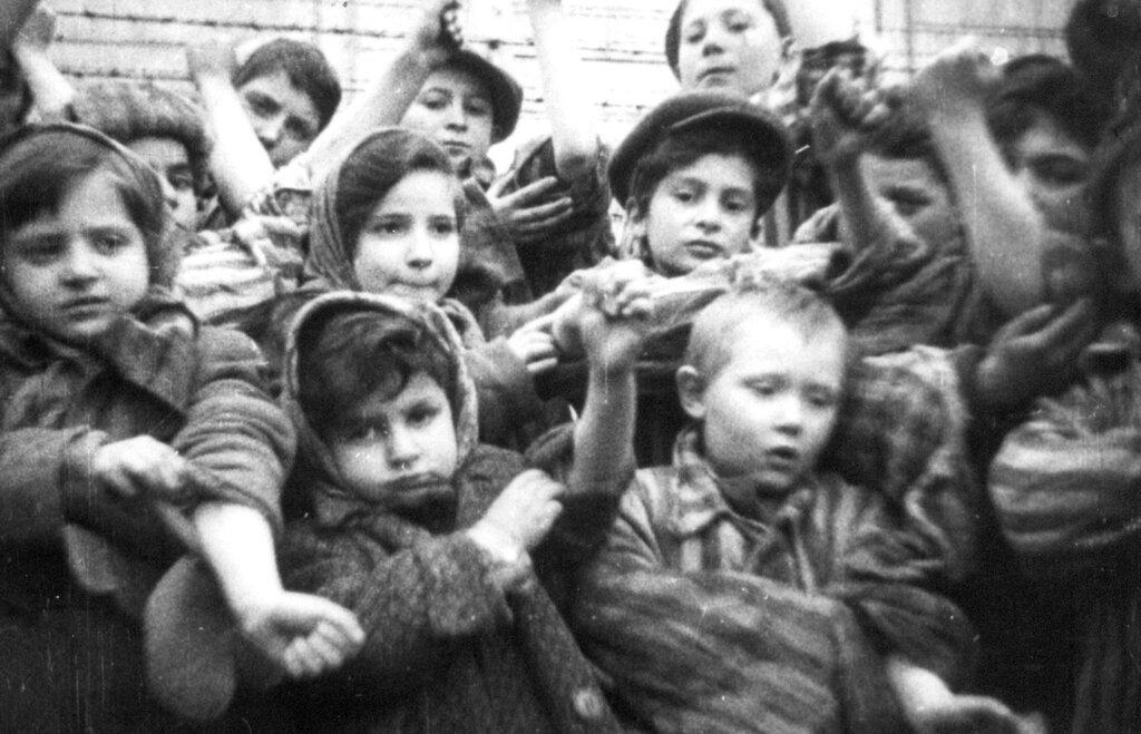 Освобожденные дети, заключенные концлагеря Освенцим (Аушвиц) показывают лагерные номера, вытатуированные на руках. Бжезинка, Польша. Февраль 1945 г.