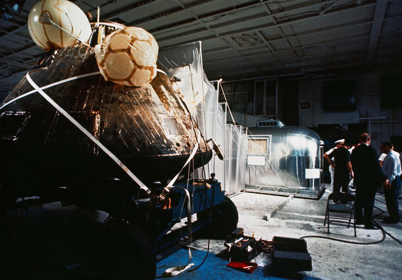 Из вертолёта астронавты перешли в мобильный карантинный фургон, где их ожидали врач и техник. На снимке:«Колумбия» и карантинный фургон на борту авианосца «Хорнет»