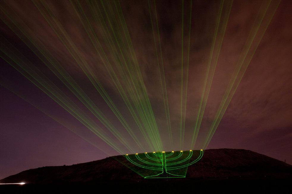 22. Лазер бьет в небо в виде меноры на холме Хирия – бывшей свалке, рядом с Тель-Авивом. (AP /
