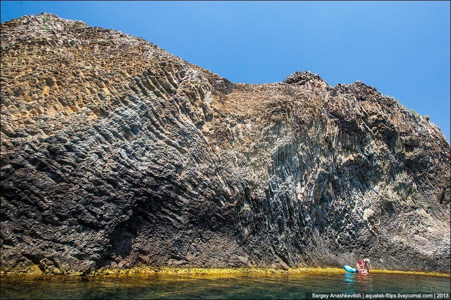 По обе стороны мыса в береговом обрыве на протяжении нескольких километров видны застывшие потоки ла