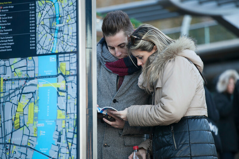London, England - March 17, 2016: Two people at the Welcome To the City of London Map in the St Paul's district of London, England. In 2016 there were almost 17m overseas visitors to the city.