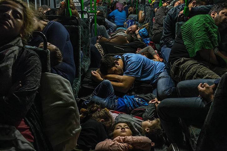 Ахмад Маджид в синей футболке в центре спит на полу автобуса вместе со своими детьми, братом Фаридом