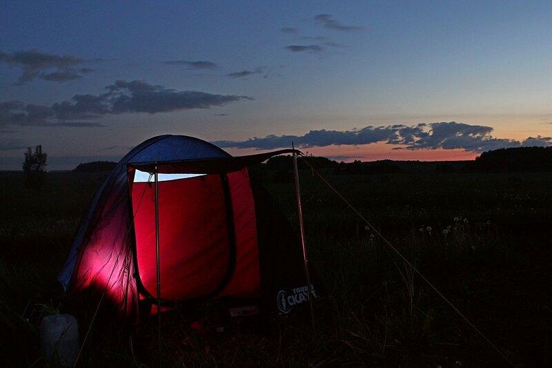 Светящаяся изнутри палатка ночью на фоне закатного неба