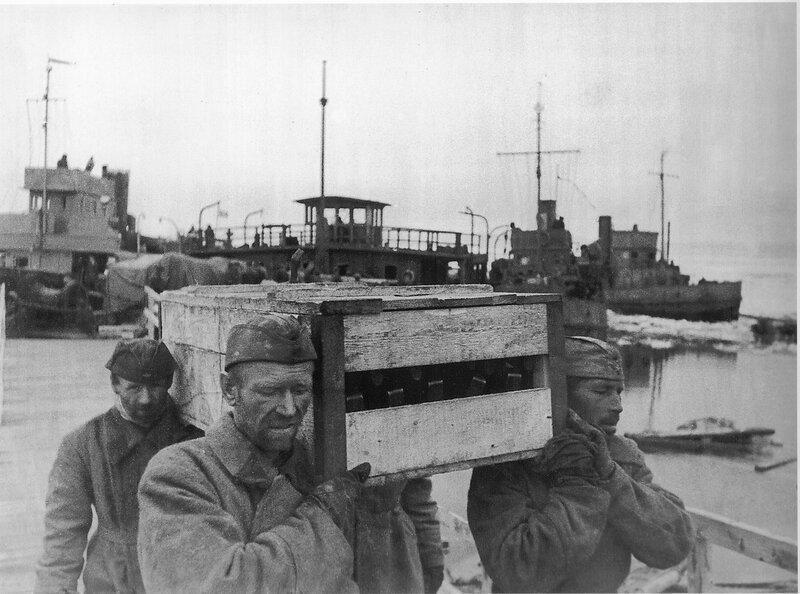 Советские солдаты выгружают ящики с оружием, доставленные по Дороге жизни