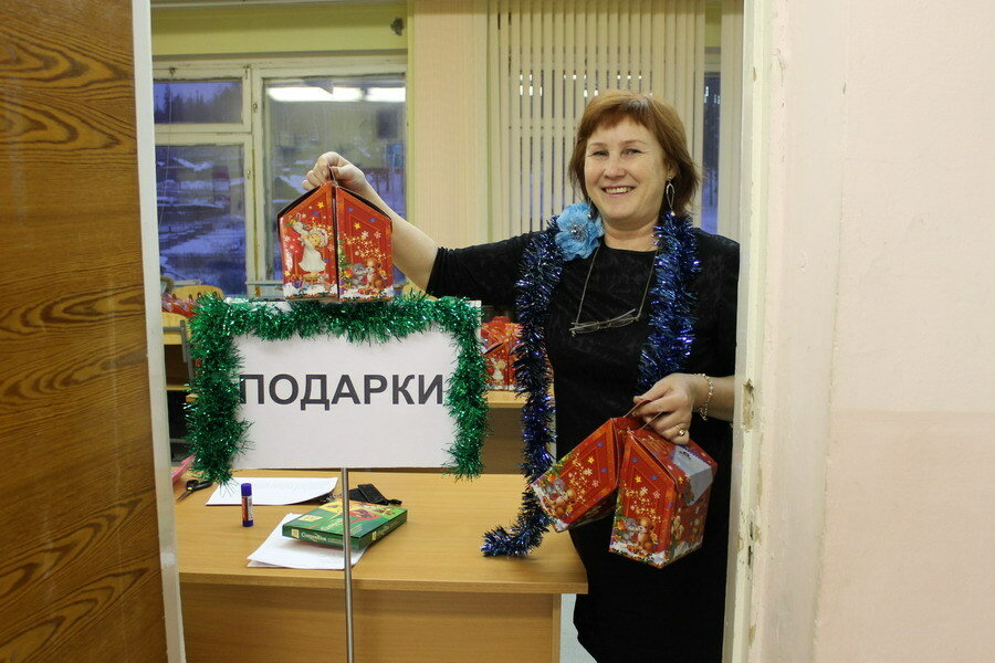 Любовь Анатольевна раздаёт подарки.