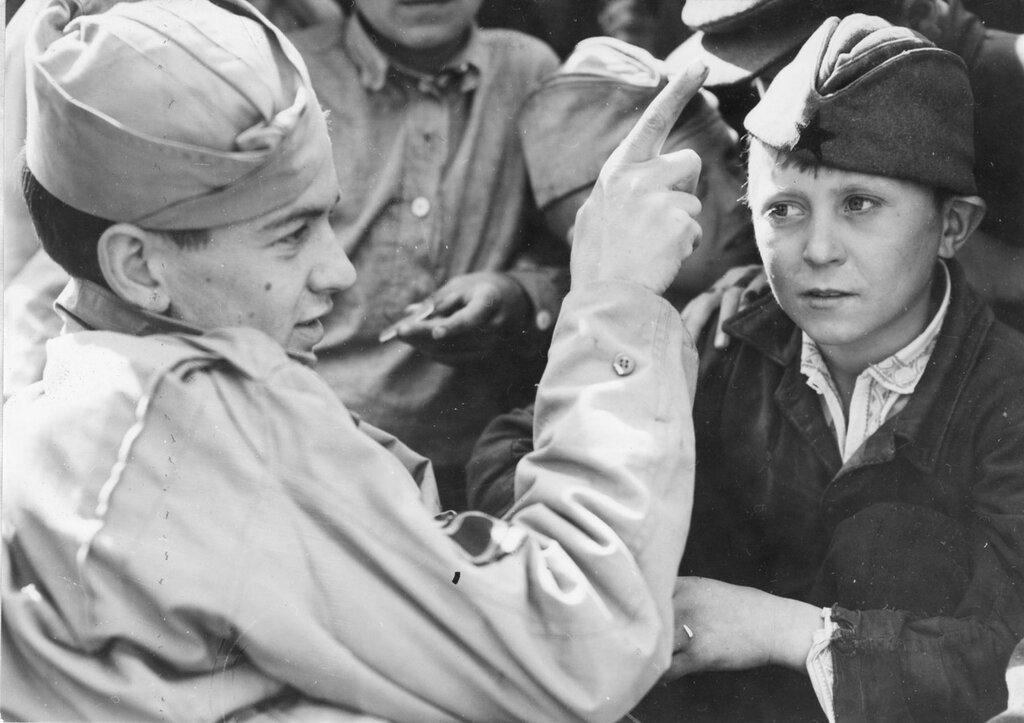 Техник-сержант Джозеф Е. Томпсон учит советского мальчика английским словам. 1944 г.