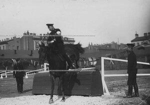 Офицер на лошади берет барьер во время конных состязаний.
