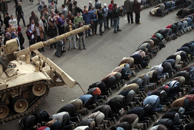 Egyptian anti-government protesters pray in front of an Egyptian army tank during a protest in Tahrir square in Cairo, Egypt.