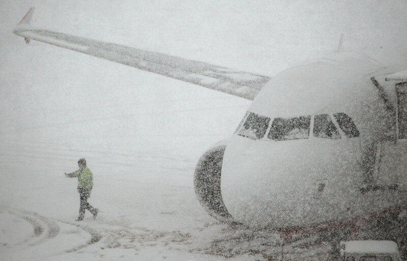 A worker walks past a plane parked on the snow covered tarmac of Zurich airport in Kloten
