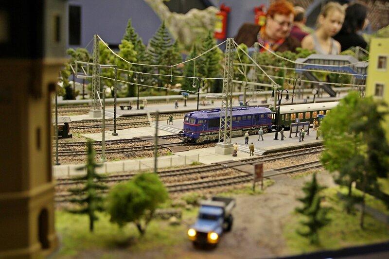 Гранд макет: пригородная платформа с электричкой, водонапорная башня, грузовик и гигантские зрители на фоне