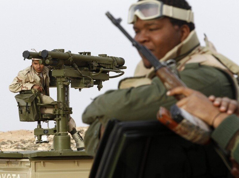 A Libyan government soldier stands at the west gate of  town Ajdabiyah