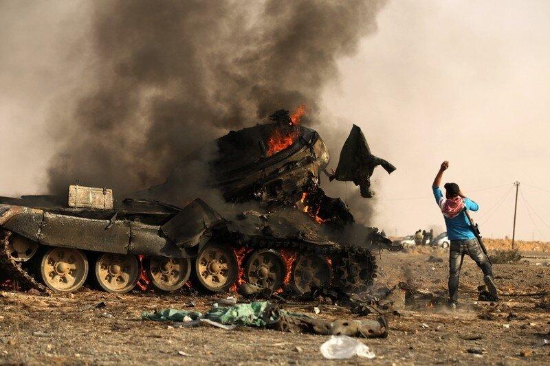 A Libyan rebel throws Libyan army unifor