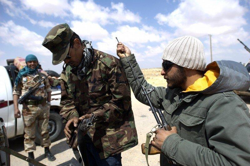 Libyan rebels clean their weapons close