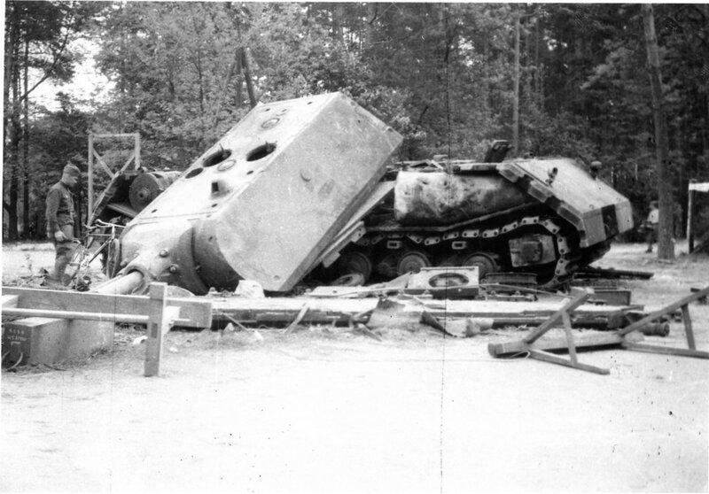 Советский солдат осматривает подорванный экспериментальный немецкий сверхтяжелый танк Маус Porsche Type 205 2 на полигоне в Куммерсдорфе.jpg