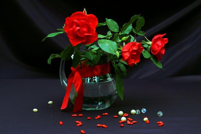Красные розы в прозрачном кувшине