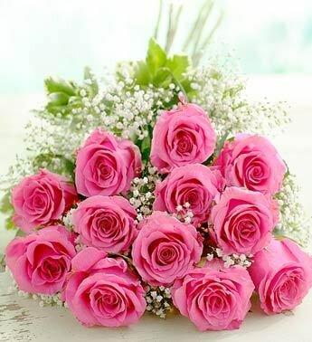 Большой букет розовых роз с белыми мелкими цветочками лежит на столе открытка поздравление картинка