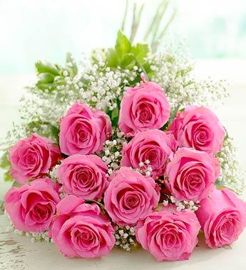 Великий букет рожевих троянд з білими дрібними квіточками лежить на столі листівка фото привітання малюнок картинка